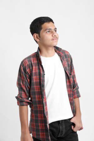Young indian boy in a casual outfit and showing expression on white background. Imagens