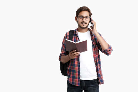 Indian college student talking on smartphone on white background.