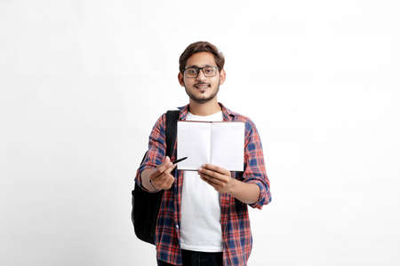 Education concept : Indian college student holding bag and showing note book on white background. Imagens