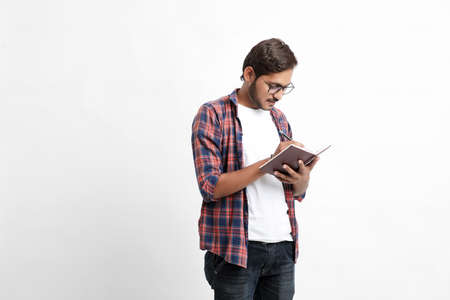 Indian college student reading book on white background. Imagens