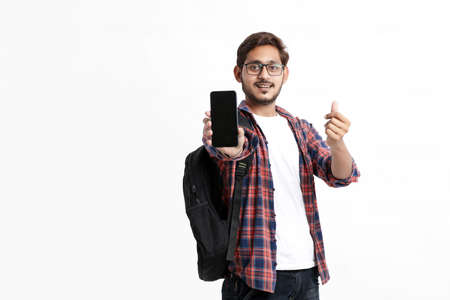 Young indian college student showing smartphone screen on white background.