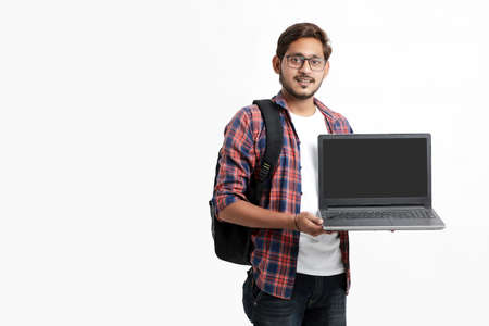 Indian college student showing laptop screen on white background. Imagens