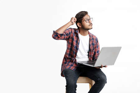 Young indian man thinking some idea when working on laptop. Imagens
