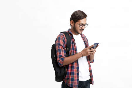Indian college student using smartphone on white background.