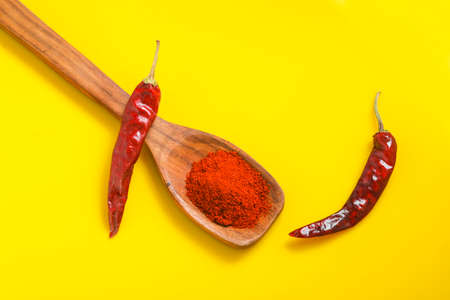 Chilli powder in wooden spoon with dry red chilly on yellow background. Imagens