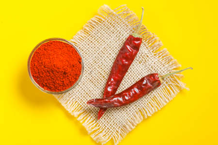 Red chilli powder in glass bowl on yellow background. top view
