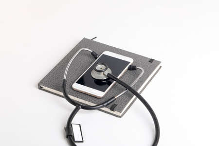Smartphone and stethoscope on white