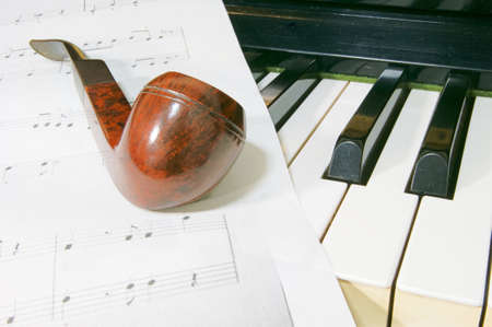 sheet music: Wooden pipe and sheet music and piano