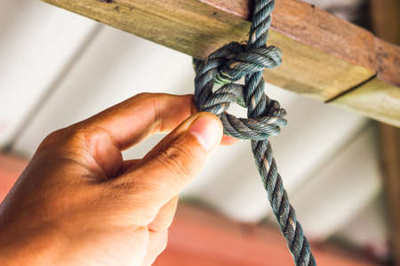 Male hands tie a rope tree,Rope knot line tied together with nature background,as a symbol for trust, teamwork or collaboration. Stock Photo