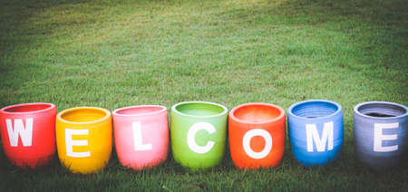 Welcoming and greetings concept with welcome word colorful on garden backgroun