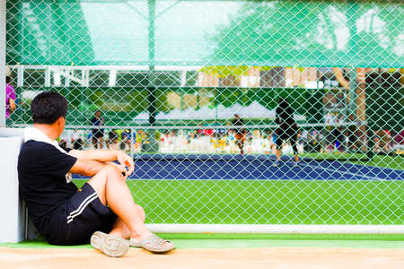 Men to watch from the outside of the wire mesh sports (competition sports tennis)