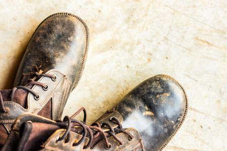 Vieilles chaussures en cuir noirs sur le sol. paire de vieilles chaussures de daim en cuir blanc Banque d'images - 99203226