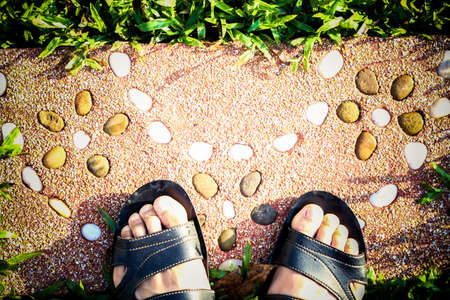 shoe foot on River stone , Stone background, Stone in the Park, Stone floor texture ,Sea stones background
