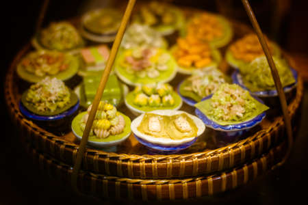 close up Miniature clay figurine Thailands floating market,Miniature boat carrying tropical fruit on wood background