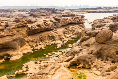 Unseen Thailand landscape view of Rock holes Stone in Sam-Pan-Bok Grand Canyon or the mekong river in thai grand canyon with sunrise in Ubon Ratchathani, Thailand.
