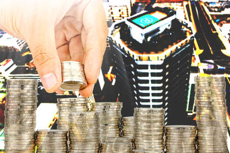 Exposure of Finance and Saving money banking concept, Hope of investor concept, Male hand putting money coin like stack growing business. background the city Imagens
