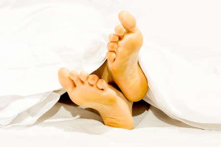 Close-up twee voeten op het bed een witte achtergrond met thuis slapen ontspannen in de vakantie.