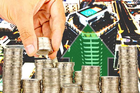 Exposure of Finance and Saving money banking concept,Hope of investor concept, Male hand putting money coin like stack growing business. background the city Imagens