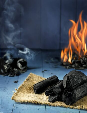 Charcoal, fire and smoke on blue wood Stock Photo
