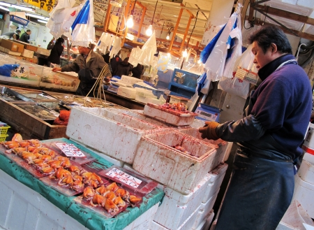 TOKYO - MARCH 23, 2012: Seafood merchant sell fish and seafood in Tsukiji fish market. It is the biggest wholesale seafood market in Tokyo, Japan.