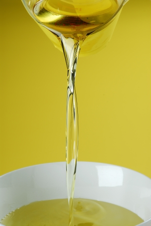 Pouring oil or golden liquid on yellow background