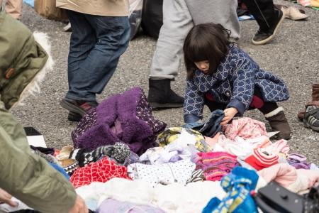 harajuku: Harajuku, Japan - December 8, 2013  Unidentified children choose the second hand clothes at flea market in Yoyogi Park, Harajuku  It is the winter flea market in the city of fashion Harajuku, Japan