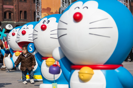 Yokohama, Japan - March 9, 2014  Unidentified child takes a photo with Doraemon figure in the 80th anniversary and new cartoon movie of Doraemon at Red Brick Warehouse, Yokohama, Japan