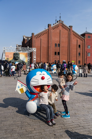 Yokohama, Japan - March 9, 2014  Unidentified children takes a photo with Doraemon figure in the 80th anniversary and new cartoon movie of Doraemon at Red Brick Warehouse, Yokohama, Japan