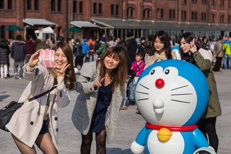 Yokohama, Japan - March 9, 2014  Unidentified girls take a photo with Doraemon figure in the 80th anniversary and new cartoon movie of Doraemon at Red Brick Warehouse, Yokohama, Japan