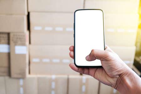 Halten Sie ein Smartphone online für den Verkäufer. Kleinunternehmen KMU-Unternehmer. Arbeiten mit Smartphone für Online-Verkäufer. Geschäft Online-Verkäufer. braune Verpackungsbox zum Senden an den Kunden.