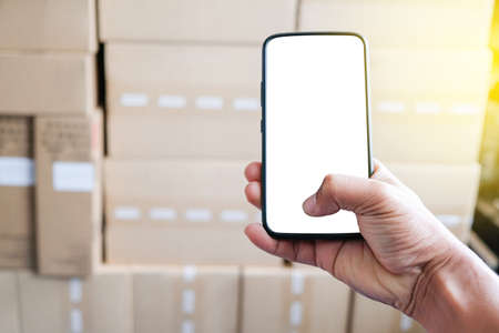 Holding a Smart phone using online for seller. Small Business SME entrepreneur. working with smartphone for online seller. business online seller. brown packaging box to send client.