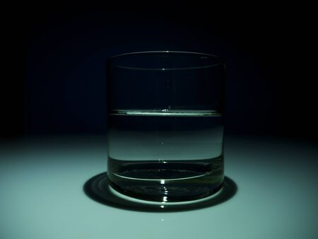 Half full glass with water on the dark. Black background Imagens
