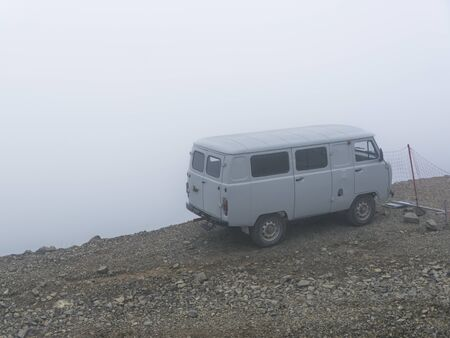Car on the brink of an abyss in the fog of the clouds. Caucasus mountains Фото со стока