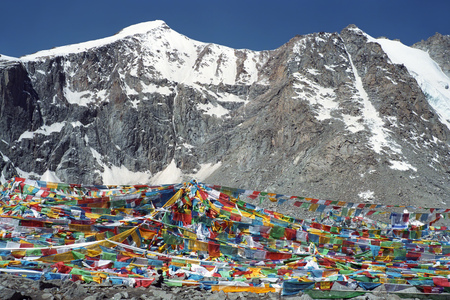 Tibetan prayer flags Lungta on the Drolma La Pass with altitude of 5,650 meters above sea level is the highest point of the ritual route around the Sacred Mount Kailash in Western Tibet.