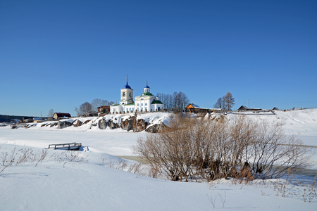 View to Russian Orthodox St. George Church was founded in 1806 year on the shore of frozen Chusovaya river in Sloboda village, Sverdlovsk region, Russia in the beginning of Spring.