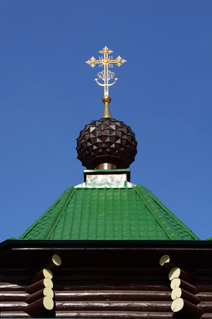 The dome with cross of Russian Orthodox Christian Gate Church in Ganina Yama Monastery against the sky, Yekaterinburg, Russia.