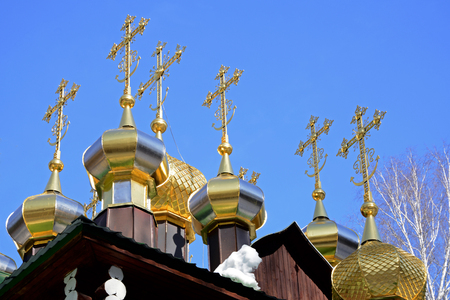 wicket door: Gold-plated domes with crosses of wooden Russian Orthodox Christian Church of St. Nicholas in Ganina Yama Monastery on early Spring, Ekaterinburg, Russia.