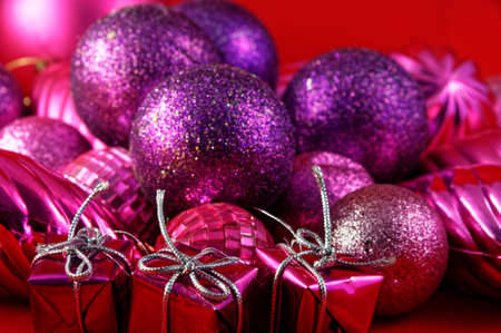Boxed gifts tied with silver string sit in front of purple and pink Christmas baubles