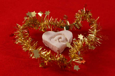 A hand crafted heart is surrounded by gold tinsel