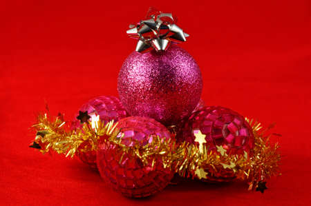 Purple and pink round Christmas baubles with a silver star on top and gold tinsel in front