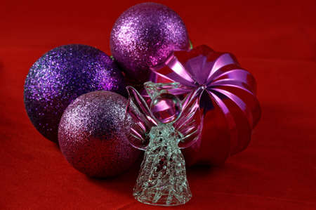 A glass angle stands in front of Christmas baubles