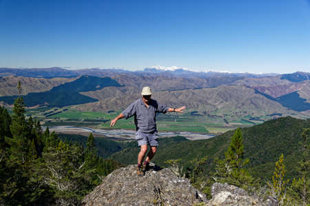 A man enjoys a jig on top of a rocky outcrop with valley and mountain behind