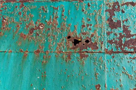 Teal paint on a huge metal door is peeling and rusting