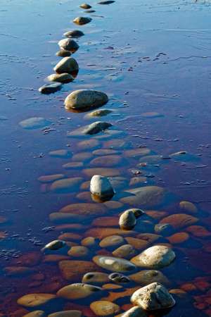 Stones in water with stones visible underneath