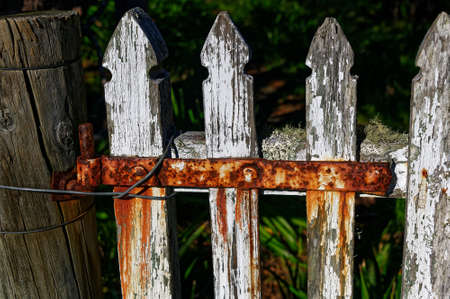 A white picket fence with a rusty red hinge