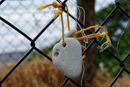 A natural piece of art, a stone tied to a fence at the seaside.
