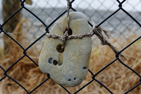 Natural art, using a stone's natural holes to tie it to a wire fence
