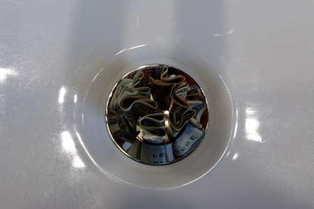 A plug hole in a white basin