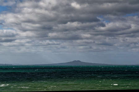 The volvanic island, Ranitoto sits under a very moody, cloudy sky