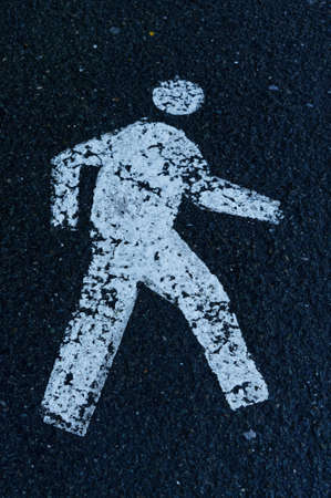A white stencil of a person on a footpath indicating which way to walk